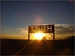 "Photo of a sunrise behind a road sign that says ""Truth"""